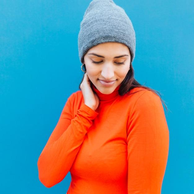 Portrait, timide, femme, regarder, porter, tricot, bonnet, contre, fond bleu Photo gratuit