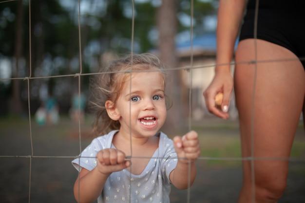 Portrait tonique de la petite fille triste regarde à travers une clôture métallique Photo Premium