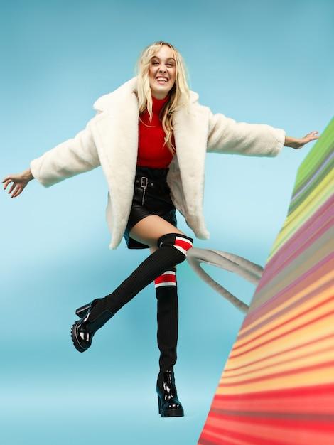 Portrait De Toute La Longueur D'une Belle Femme Blonde Drôle Souriante Marchant Avec Des Sacs Colorés Isolés Sur Fond Bleu Studio. Photo gratuit