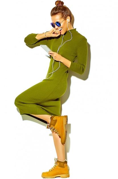 Portrait De Toute La Longueur De La Belle Femme Brune Souriante Mignonne Heureuse Dans Des Vêtements D'été Décontractés Hipster Vert Isolé Sur Blanc, écouter De La Musique Dans Un Smartphone Avec Un Casque Photo gratuit