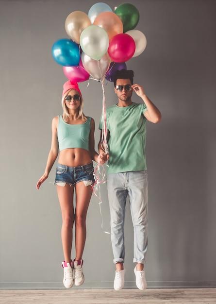 Portrait de toute la longueur d'élégant jeune couple à lunettes de soleil. Photo Premium