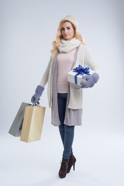 Portrait de toute la longueur de la jeune femme caucasienne recherchant des cadeaux Photo gratuit
