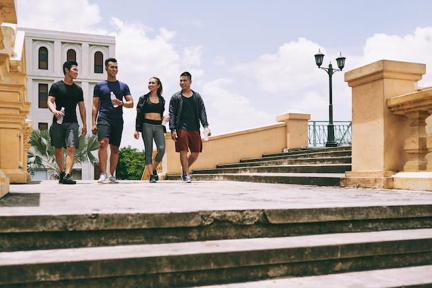 Portrait de toute la longueur de jeunes gens prenant une pause dans un exercice de jogging marchant en plein air Photo gratuit
