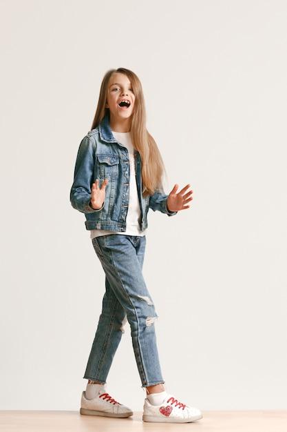 Portrait De Toute La Longueur De Mignon Petit Adolescent Dans Des Vêtements De Jeans élégants Regardant La Caméra Et Souriant Photo gratuit