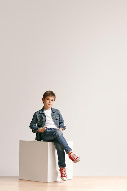 Portrait De Toute La Longueur De Mignon Petit Garçon Enfant En Jeans élégants Et Souriant, Debout Sur Blanc. Concept De Mode Pour Enfants Photo gratuit