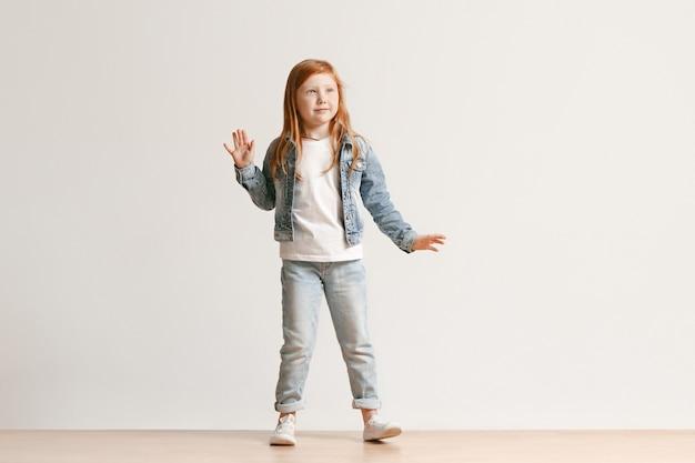 Portrait De Toute La Longueur De La Petite Fille Mignonne Enfant Dans Des Vêtements De Jeans élégants Regardant La Caméra Et Souriant, Debout Contre Le Mur Blanc Du Studio. Concept De Mode Pour Enfants Photo gratuit
