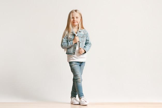 Portrait De Toute La Longueur De La Petite Fille Mignonne Enfant Dans Des Vêtements De Jeans élégants Et Souriant, Debout Sur Blanc. Concept De Mode Pour Enfants Photo gratuit