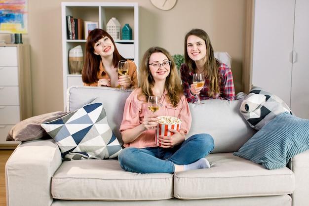 Portrait De Trois Amis De Jeunes Filles Gaies Avec Des Bols De Pop-corn Et Du Vin, Près Du Canapé élégant à La Maison. Photo Premium