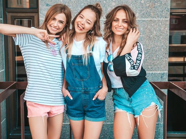 Portrait De Trois Jeunes Belles Filles Hipster Souriantes Dans Des Vêtements D'été à La Mode. Sexy Femmes Insouciantes Posant Dans La Rue.modèles Positifs S'amusant.ils Montrent La Langue Et Le Signe De La Paix Photo gratuit