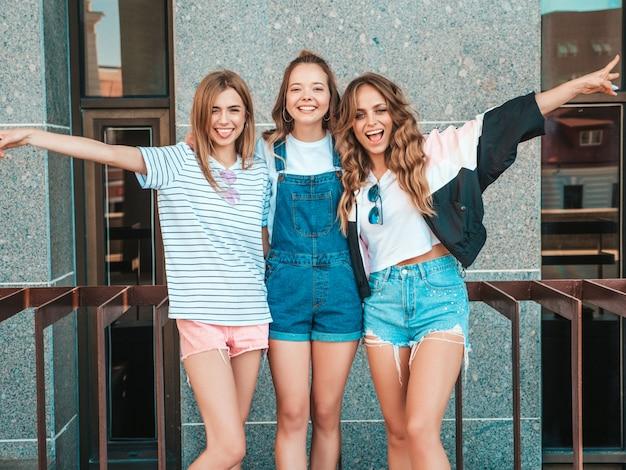 Portrait De Trois Jeunes Belles Filles Hipster Souriantes Dans Des Vêtements D'été à La Mode. Sexy, Insouciant, Femmes, Poser, Rue, Positif, Modèles, Amusement, élévation, Mains Photo gratuit