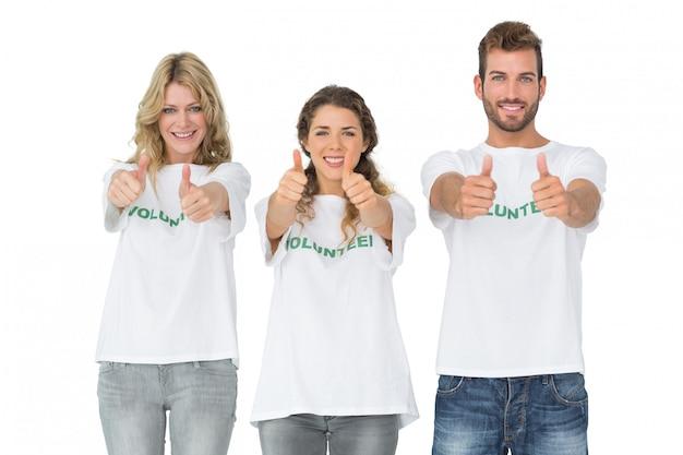 Portrait de trois volontaires heureux gesticulant pouce en l'air Photo Premium