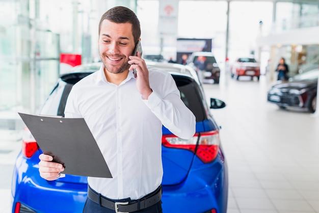 Portrait de vendeur chez un concessionnaire automobile Photo gratuit