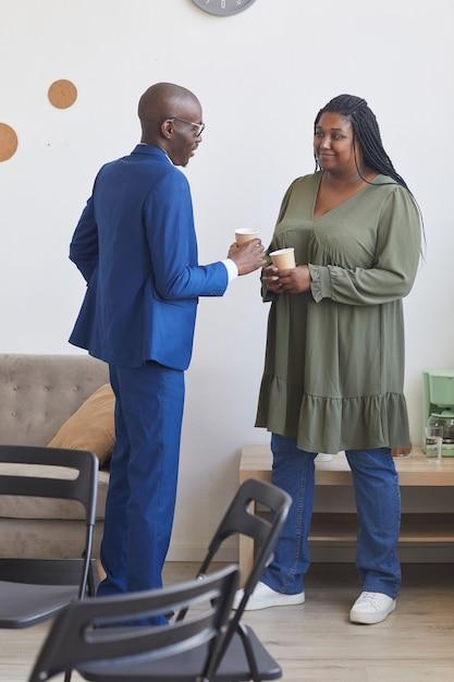 Portrait Vertical De Deux Personnes Afro-américaines Parlant Pendant La Pause-café En Réunion Du Groupe De Soutien Photo Premium