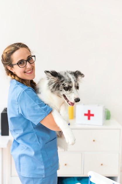 Portrait d'un vétérinaire féminin heureux avec un chien Photo gratuit