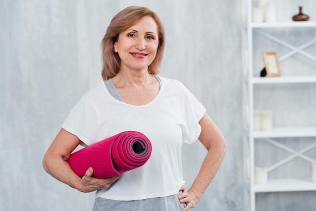 Portrait d'une vieille femme souriante tenant un tapis d'yoga roulé Photo gratuit