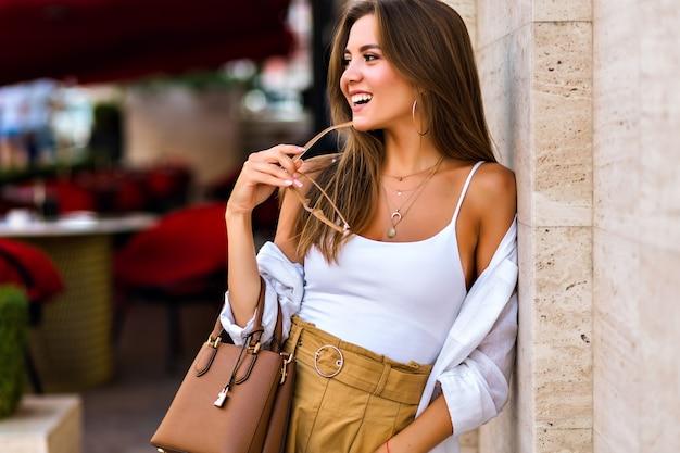 Portrait De Ville De Mode De Vie D'incroyable Jolie Jeune Femme Brune Portant Des Lunettes Claires à La Mode Beige Et Des Bijoux En Or, Des Couleurs Douces Et Chaudes, Un Style Minimalisme Photo gratuit