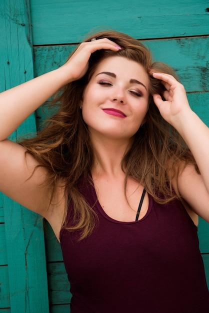 Portret D'un Modèle Fille Plus La Taille Sur L'arrière-plan D'un Mur Vert Photo Premium