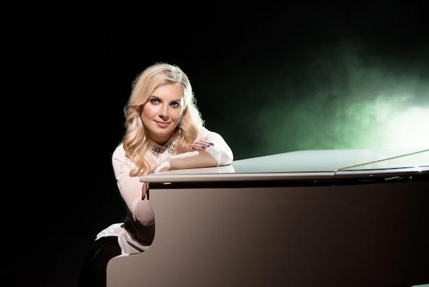 Portret De Pianiste Posant Près De Piano Blanc Sur La Scène Dans Le Faisceau De Lumière. Photo Premium