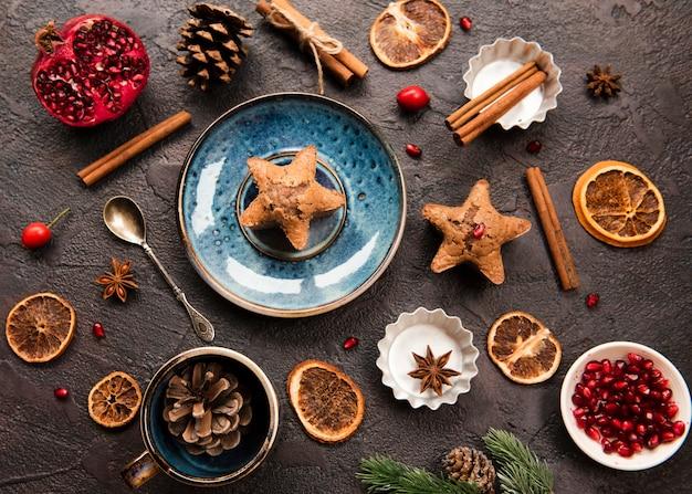 Pose à plat d'un biscuit en forme d'étoile avec des pommes de pin et de la grenade Photo gratuit