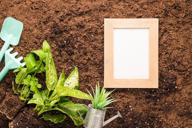 Pose à plat du cadre et des outils de jardinage avec fond Photo gratuit
