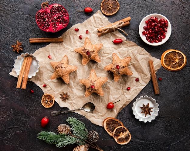 Pose plate de biscuits en forme d'étoile avec de la grenade et de la cannelle Photo gratuit