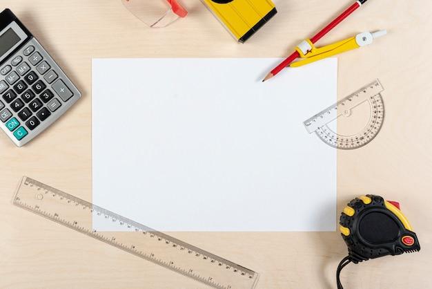 Pose plate du bureau d'architecte avec une feuille de papier Photo gratuit