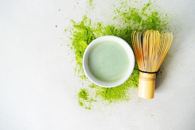 Pose plate de thé vert biologique matcha en poudre avec des outils japonais, un fouet en bambou chasen Photo Premium