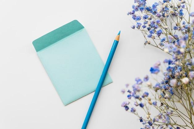 Poser avec des fleurs et une enveloppe avec un crayon Photo gratuit
