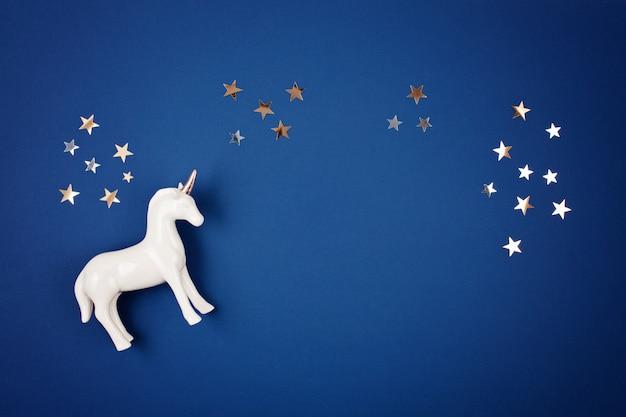 Poser avec une licorne blanche et des étoiles sur le fond bleu Photo Premium