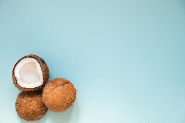 Poser à plat avec des noix de coco mûres sur bleu Photo Premium