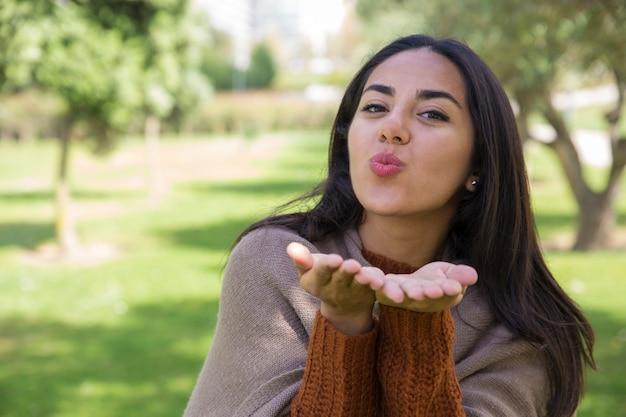 Positif jeune femme envoyant l'air kiss dans le parc de la ville Photo gratuit