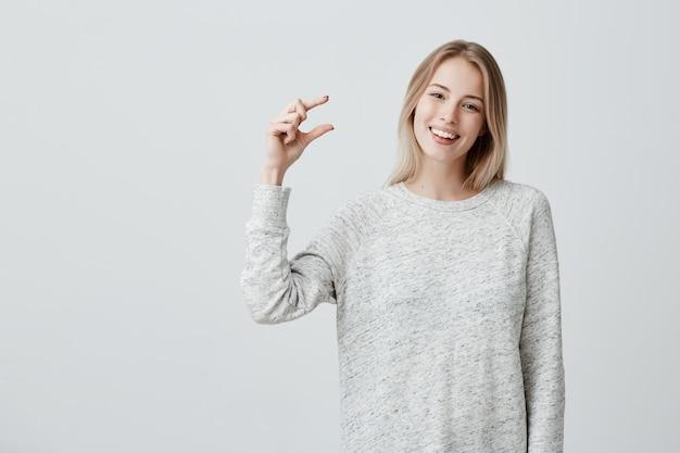 Positive Belle Femme Blonde En Pull Ample Montre Quelque Chose De Petite Taille Avec Les Mains, De Bonne Humeur Photo gratuit