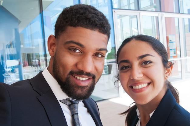 Positive collègues posant et prenant selfie photo en plein air Photo gratuit