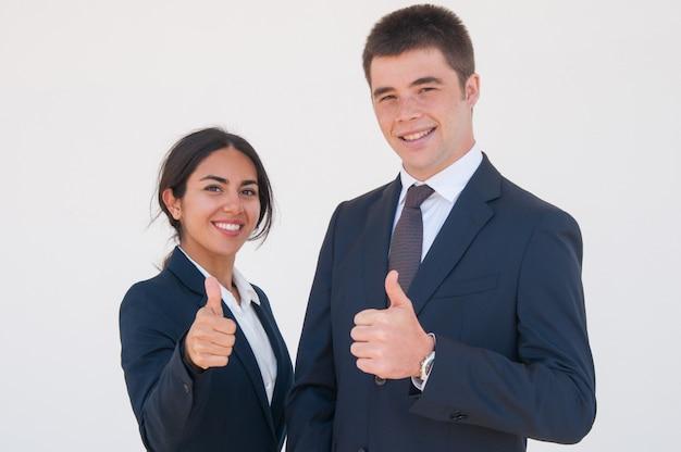 Positive confiant collègues d'affaires montrant les pouces vers le haut Photo gratuit