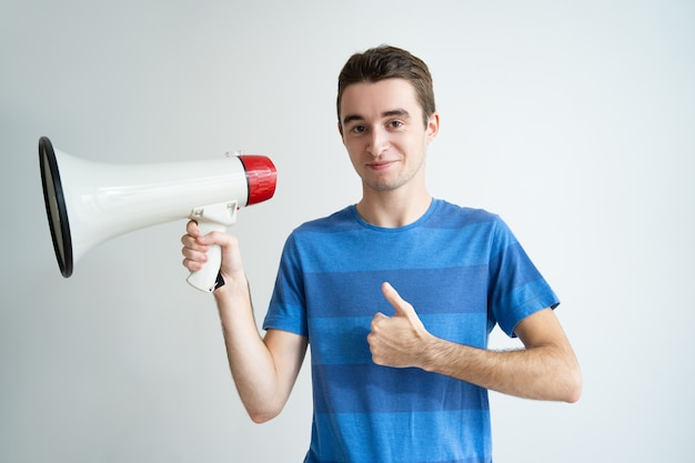 Positive homme tenant un mégaphone et montrant le pouce en place Photo gratuit