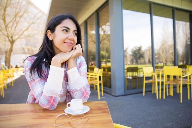 Positive jolie jeune femme appréciant de boire du café au café Photo gratuit