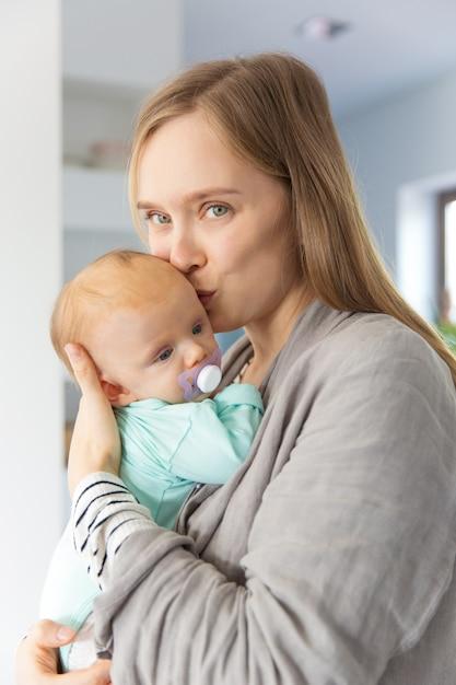 Positive Nouvelle Mère Embrassant Et Câlinant Bébé Photo gratuit