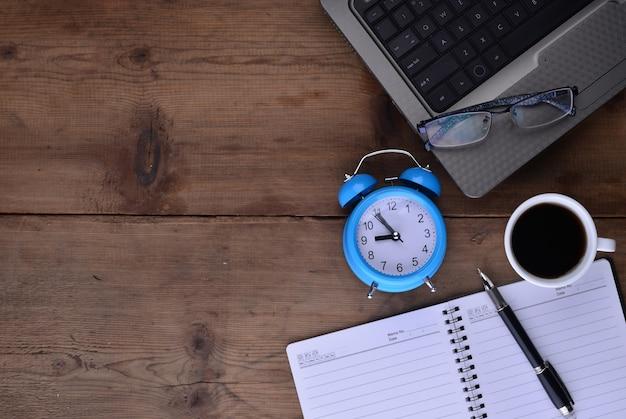 Poste de travail avec le café portable d'horloge et un ordinateur portable Photo gratuit