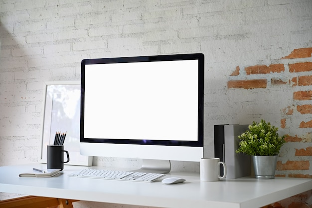 Poste de travail loft avec maquette d'écran d'ordinateur de bureau vierge et accessoires de bureau à domicile Photo Premium