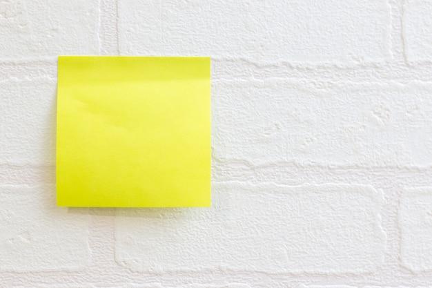 Postez-y une note ou un post-it sur le motif de briques de papier peint blanc utilisé pour Photo Premium