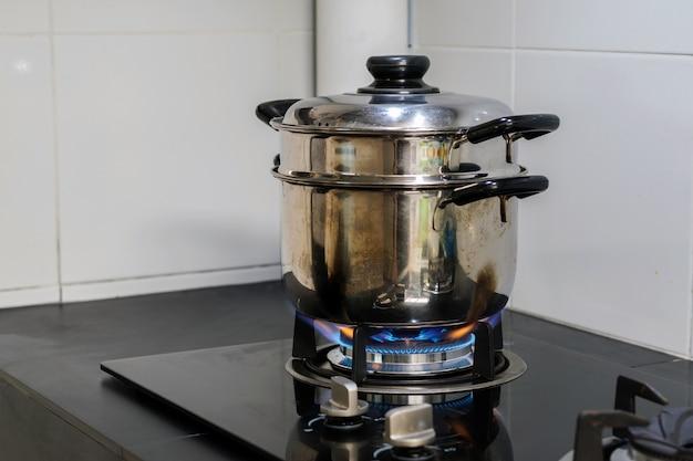 Un pot en acier inoxydable est placé sur une cuisinière à gaz. Photo Premium