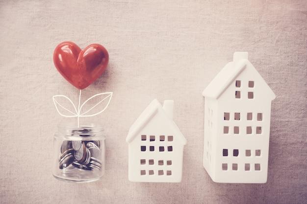 Un pot d'arbre de coeur qui pousse sur des pièces d'argent et des maisons modèles Photo Premium