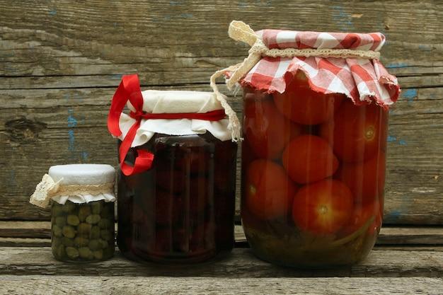 Pot Avec Des Conserves. Confiture De Fraises Maison, Tomates Marinées Et Câpres Sur Fond De Bois Photo Premium