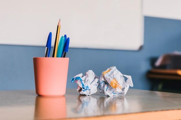 Pot à crayons et papier froissé Photo gratuit