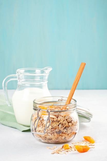 Pot avec du muesli à la granola ou à l'avoine fait maison avec des noix et des fruits secs et du lait. Photo Premium