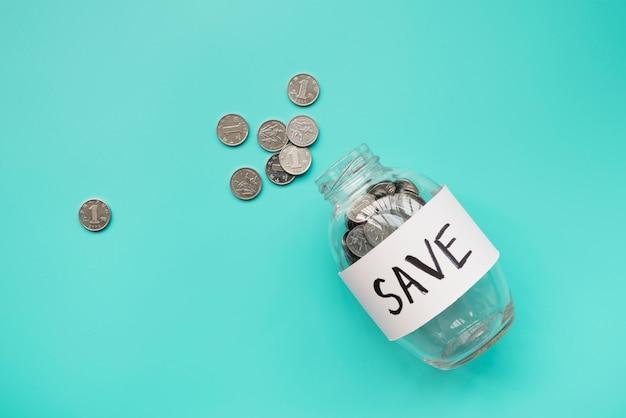 Pot d'épargne couché avec des pièces à l'extérieur Photo gratuit