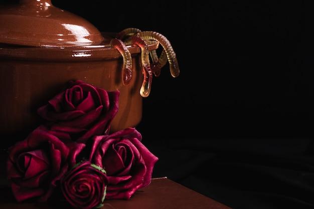 Pot de gelée et de roses sur fond noir Photo gratuit