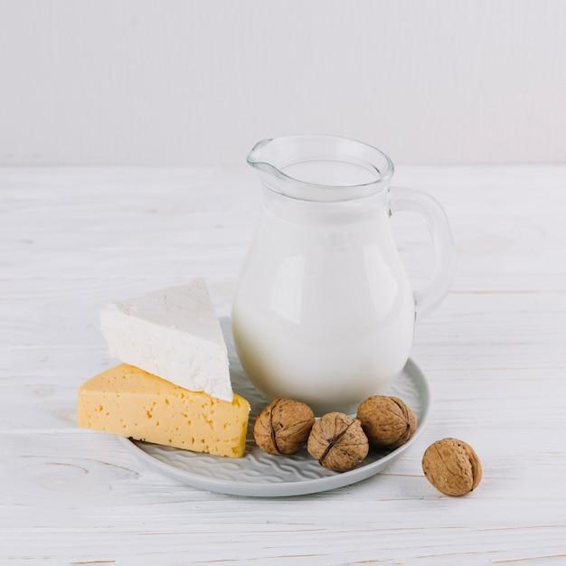 Pot de lait; fromage et noix sur une table en bois blanche Photo gratuit