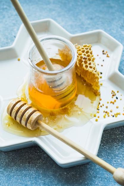 Pot de miel avec louche de miel et peigne de miel sur plateau floral Photo gratuit