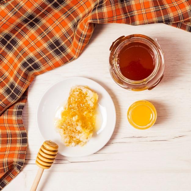 Pot de miel; nid d'abeille; louche de miel et nappe sur bureau blanc Photo gratuit